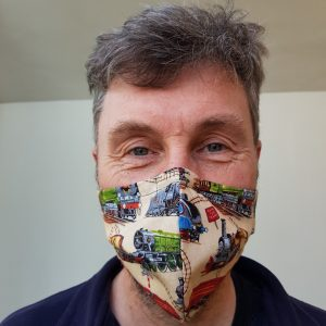 adult wearing steam train face mask in a cream colour with a variety of steam trains in different colours