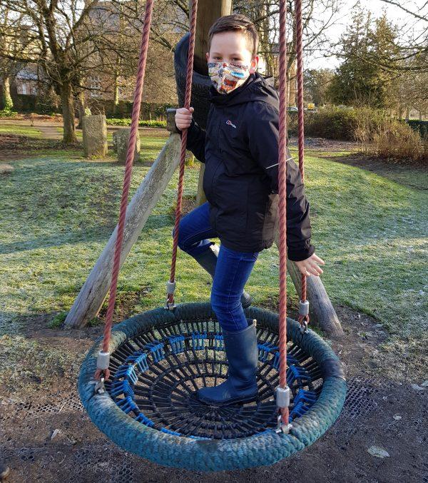 Young boy plays wearing a small adult face mask with steam trains