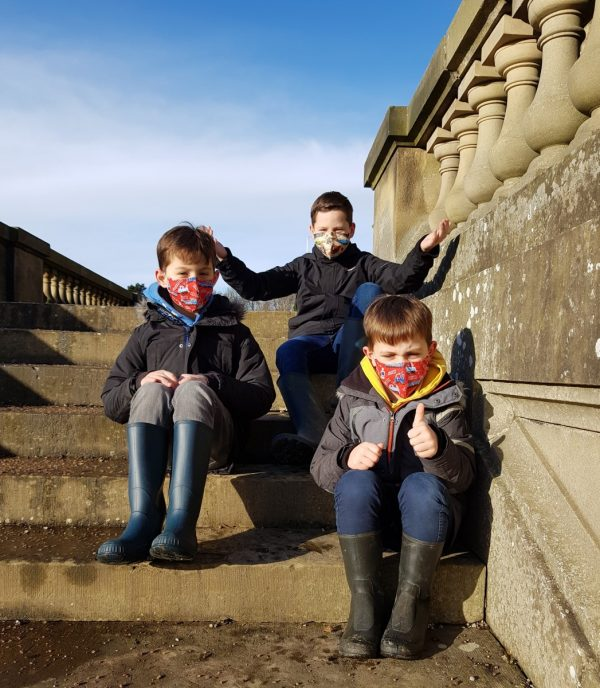Three boys sit on steps. One wears a small adult face mask, the other two wear red children's steam train masks.